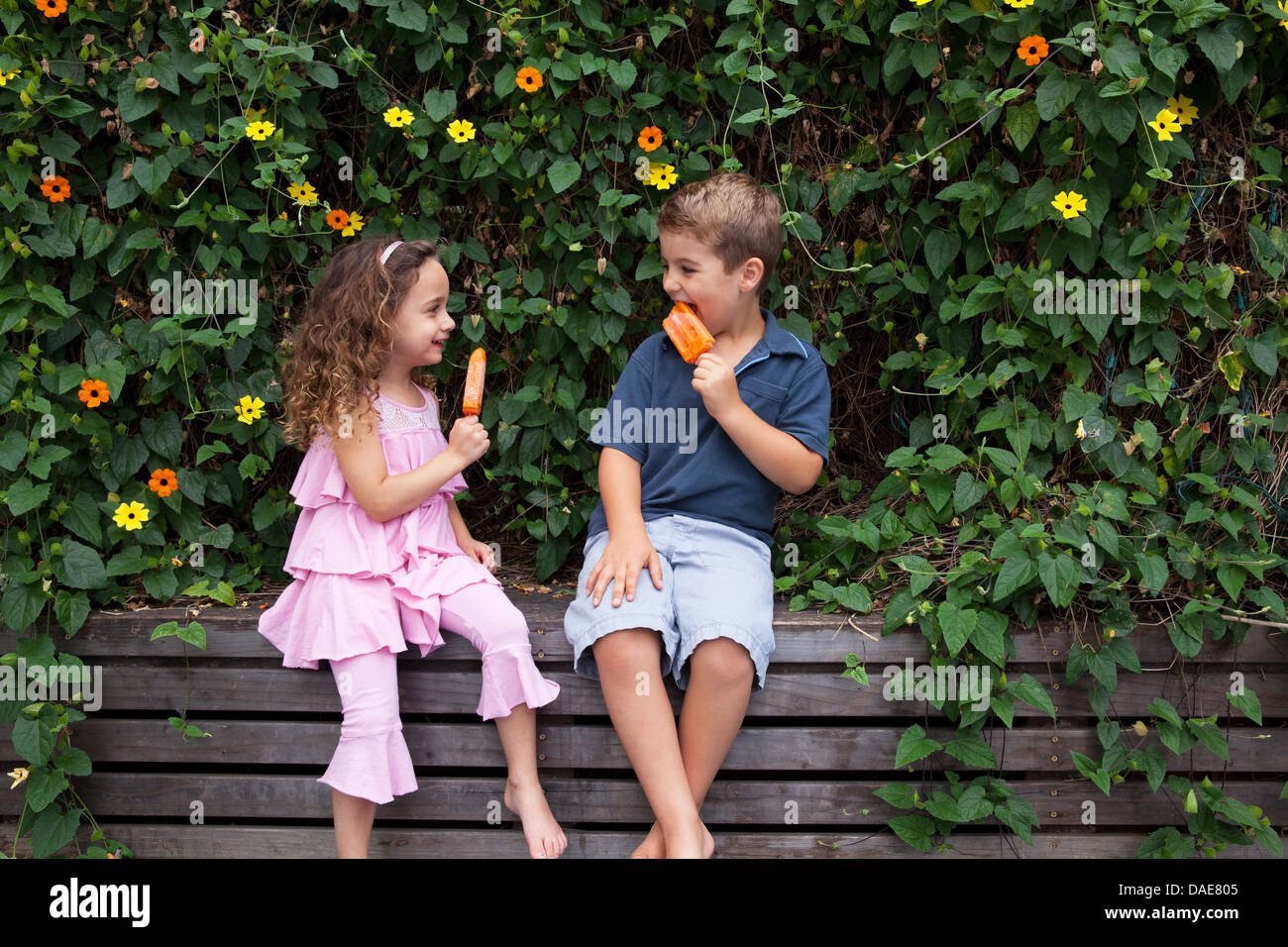 Bruder und Schwester essen Eis am Stiehl durch Pflanzen Stockbild