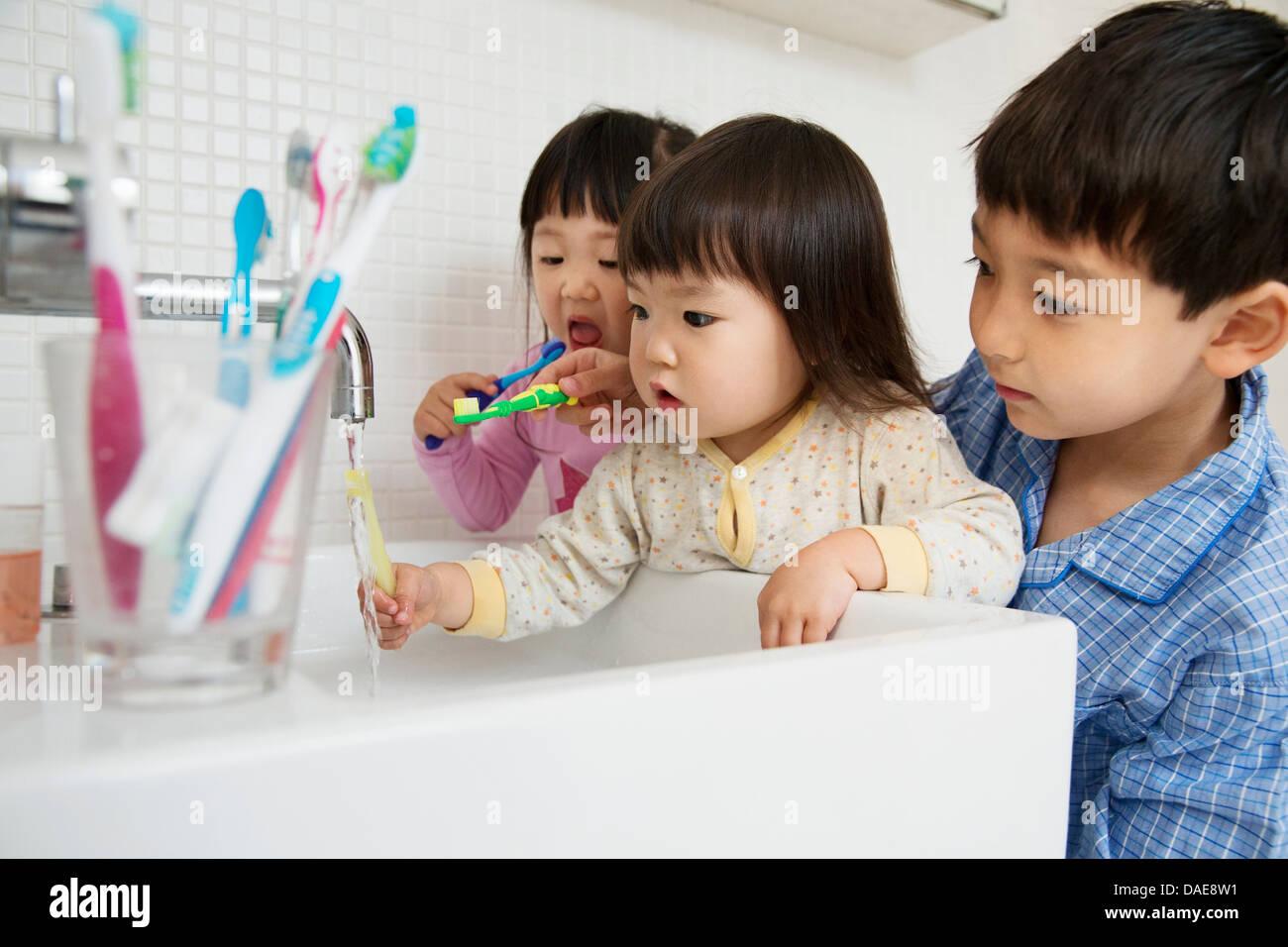 Bruder helfen, Schwestern, Zähne putzen Stockbild