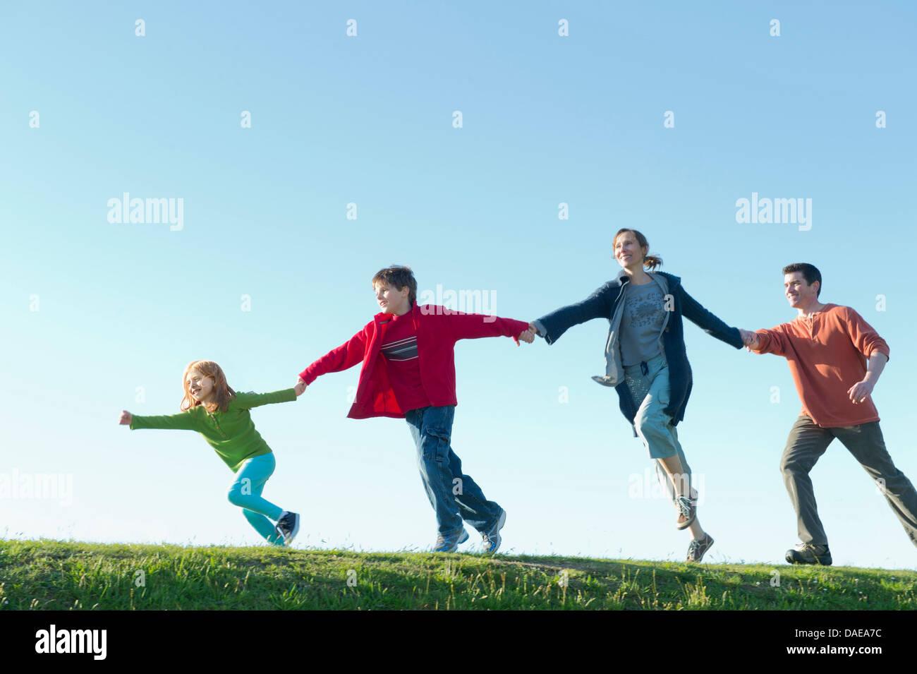 Eltern und 2 Kinder laufen und Hand in Hand Stockbild
