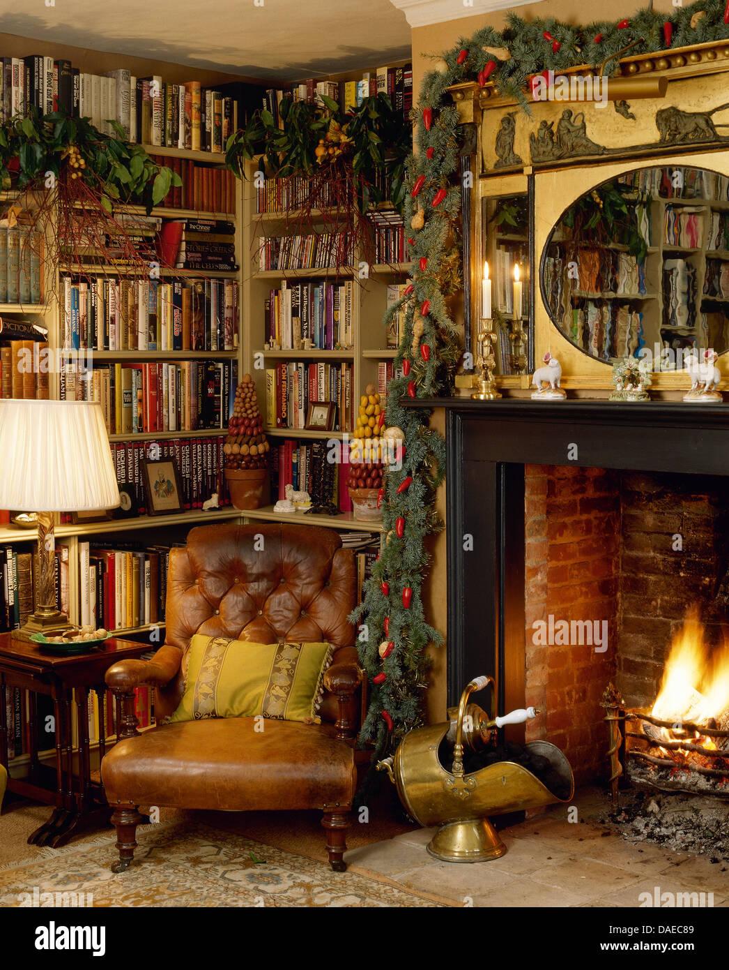 Ledersessel Vor Bücherregalen Und Kamin Mit Brennenden Feuer Im Wohnzimmer  Gemütlich Land Für Weihnachten Dekoriert