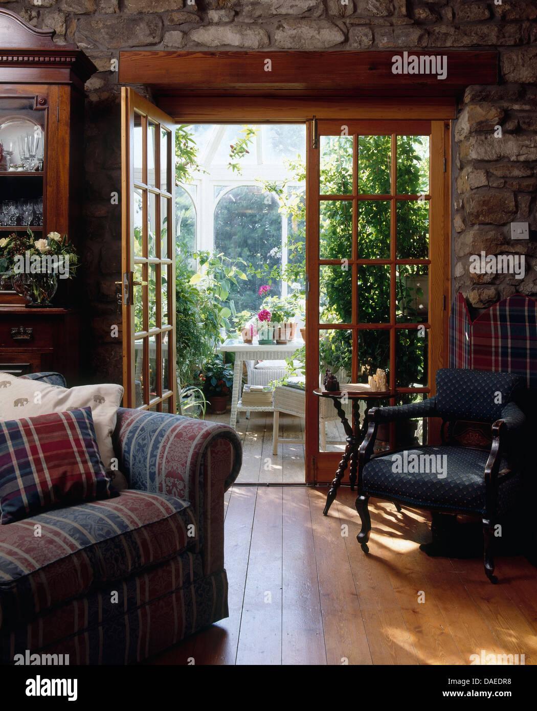 Bequemes Sofa und Sessel im Wohnzimmer mit Blick durch Doppeltür ins ...