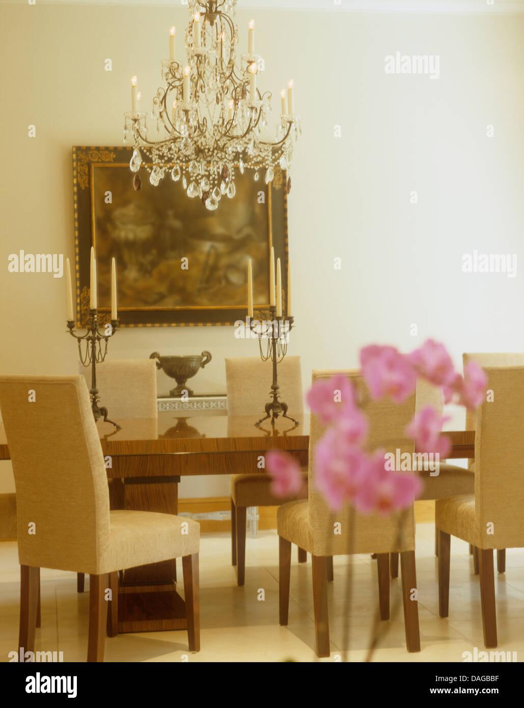 Reich Verzierte Glas Kronleuchter über Tisch Mit Beige Gepolsterte Stühle  Im Modernen Speisesaal Mit Großen Öl Gemälde An Der Wand