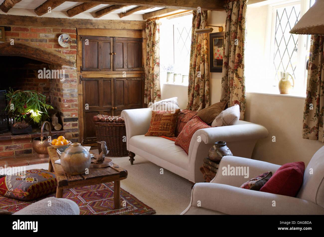 wei e sofas mit kissen und rustikale couchtisch aus holz im haus wohnzimmer mit backstein kamin. Black Bedroom Furniture Sets. Home Design Ideas