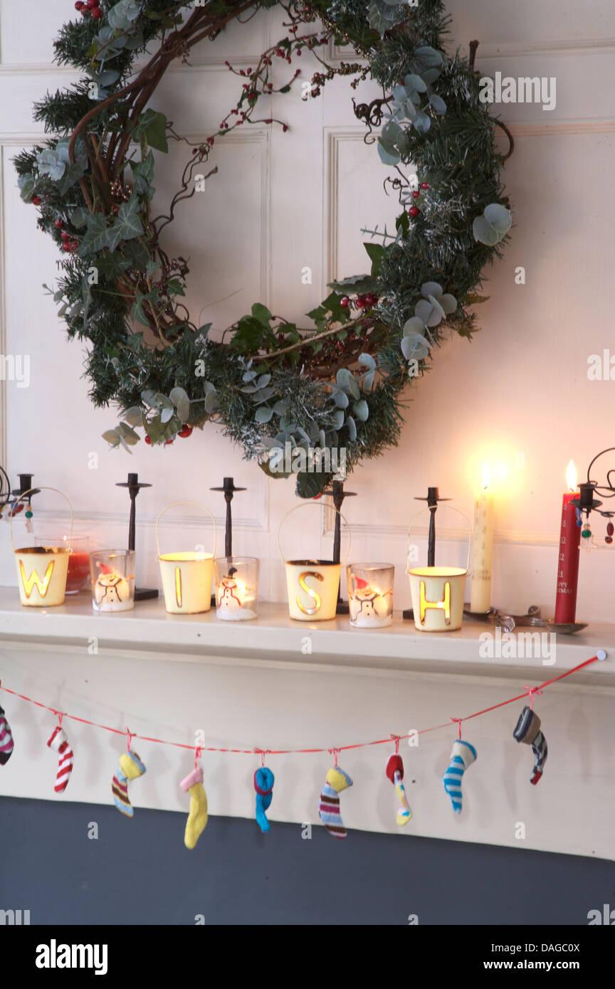 Efeu Und Koniferen Kranz über Dem Kamin Dekoriert Für Weihnachten Mit  Brennenden Kerzen Auf Kaminsims Und Girlande Aus Winzigen Strümpfe