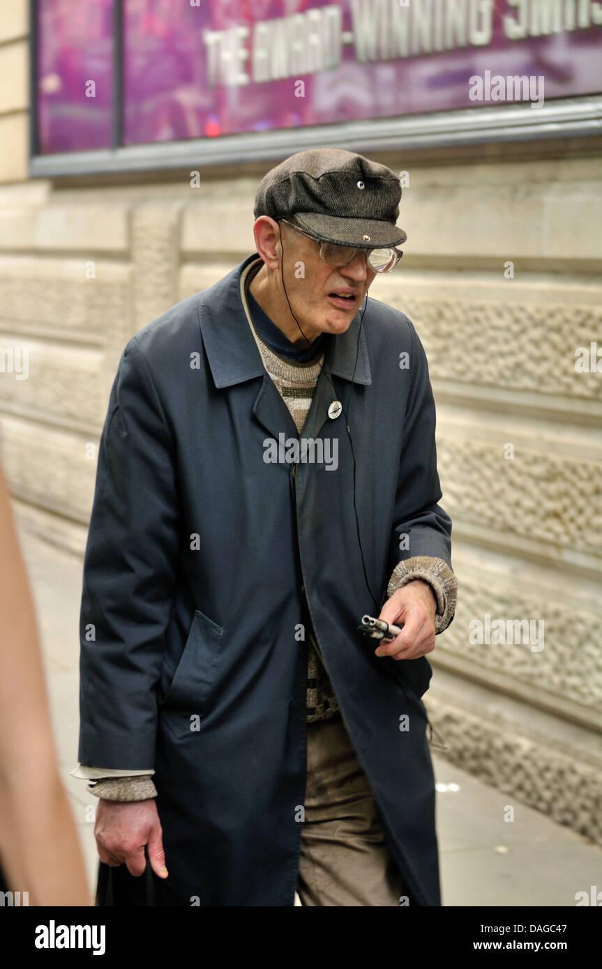 Scruffily gekleideter Mann trägt einen Regenmantel Stockbild