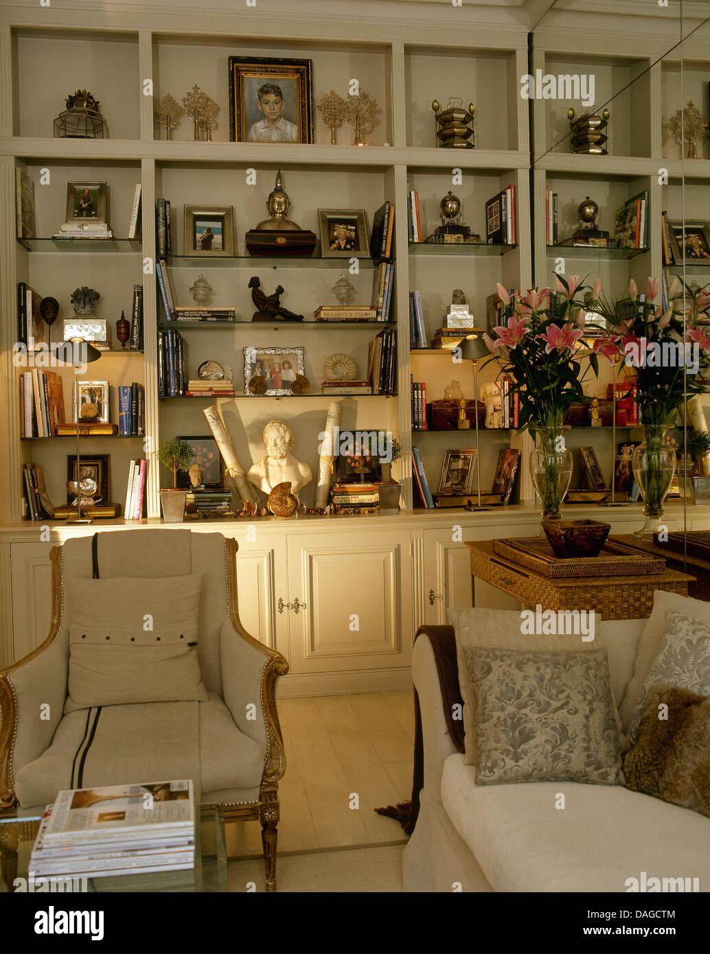 Wunderbar Sammlung Von Artefakten Auf Gebaut In Regale Im Stadthaus Wohnzimmer Mit  Cremefarbenen Sessel Und Sofa Mit Kissen Gestapelt