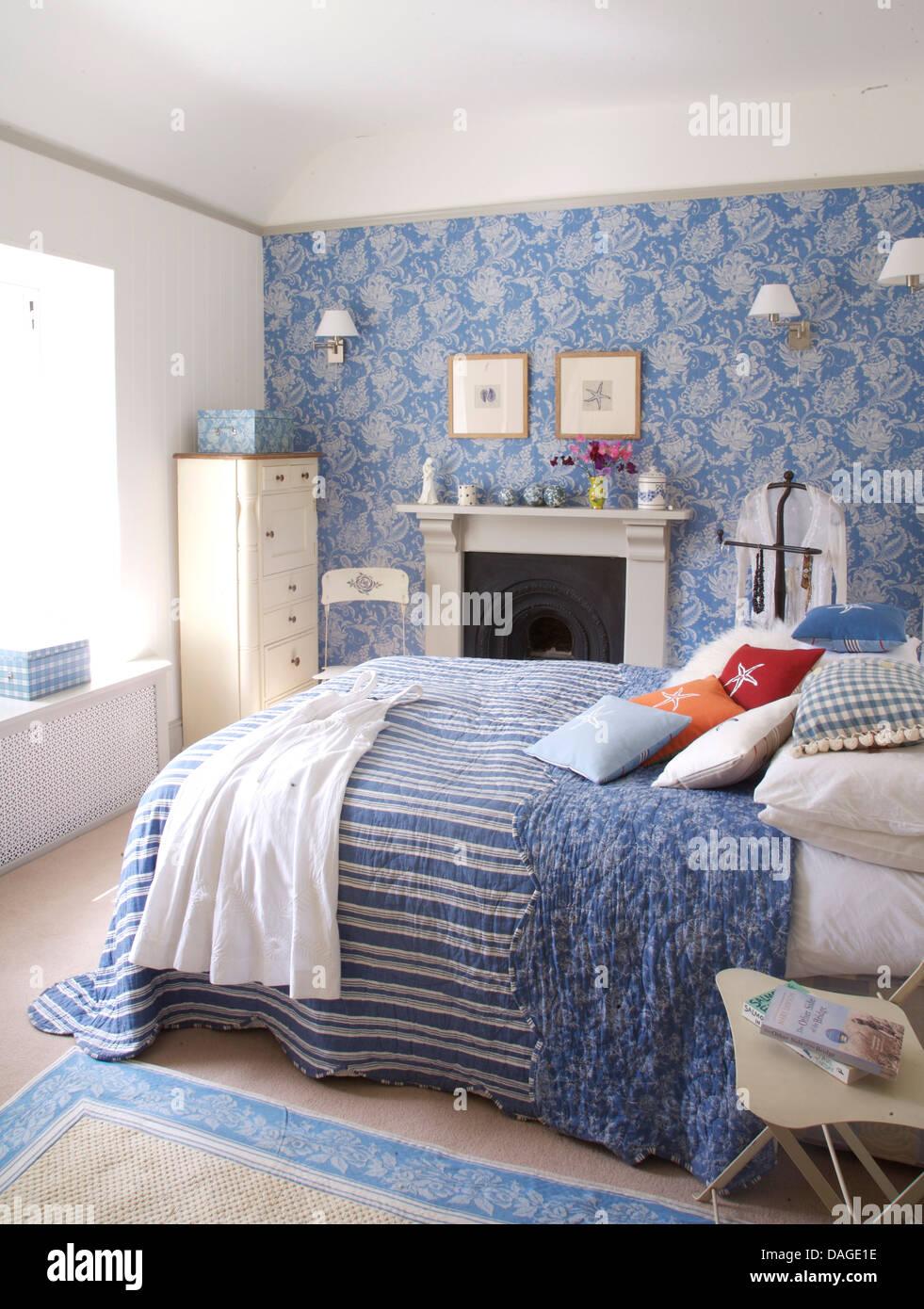 Blau Gestreifte Quilt Mit Floralen Futter In Kustennahen Schlafzimmer Mit Blau Weiss Floral Tapete An Der Wand Uber Dem Kamin Stockfotografie Alamy