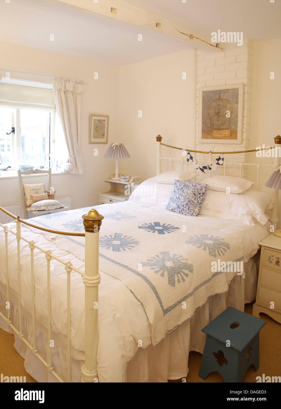Blaue Kissen und blaue + weiße Quilt Vintage Messingbett im weißen ...