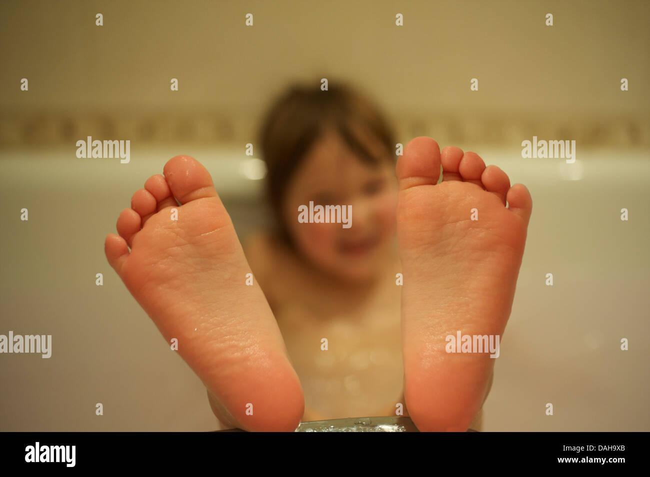 Kinderfuß ragte aus dem Bad. MODEL RELEASED Stockbild