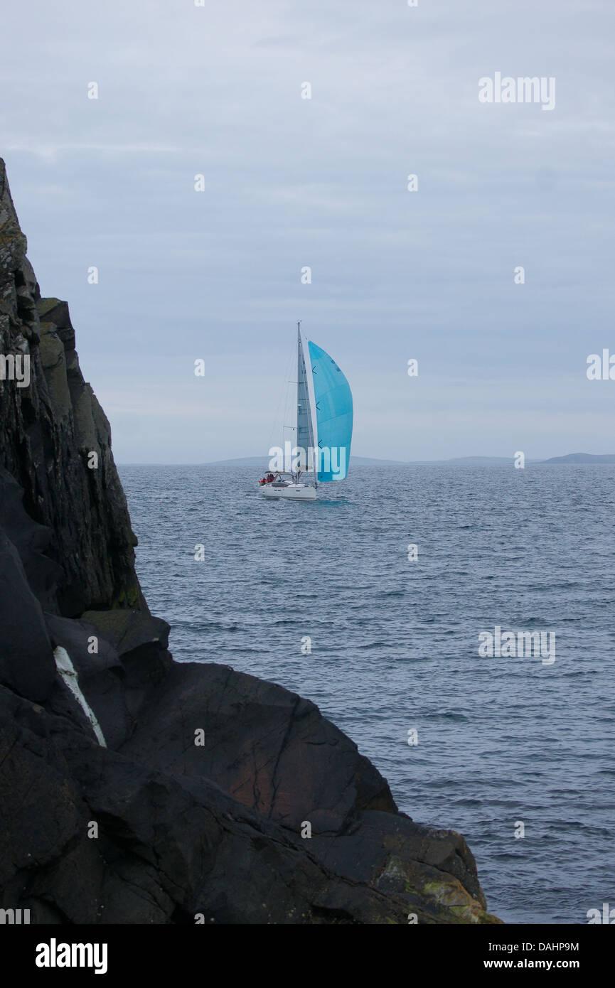 Ein kleines Segelschiff vorbei an Felsen am Rande der Insel Bressay in Richtung Hafen von Lerwick Stockbild