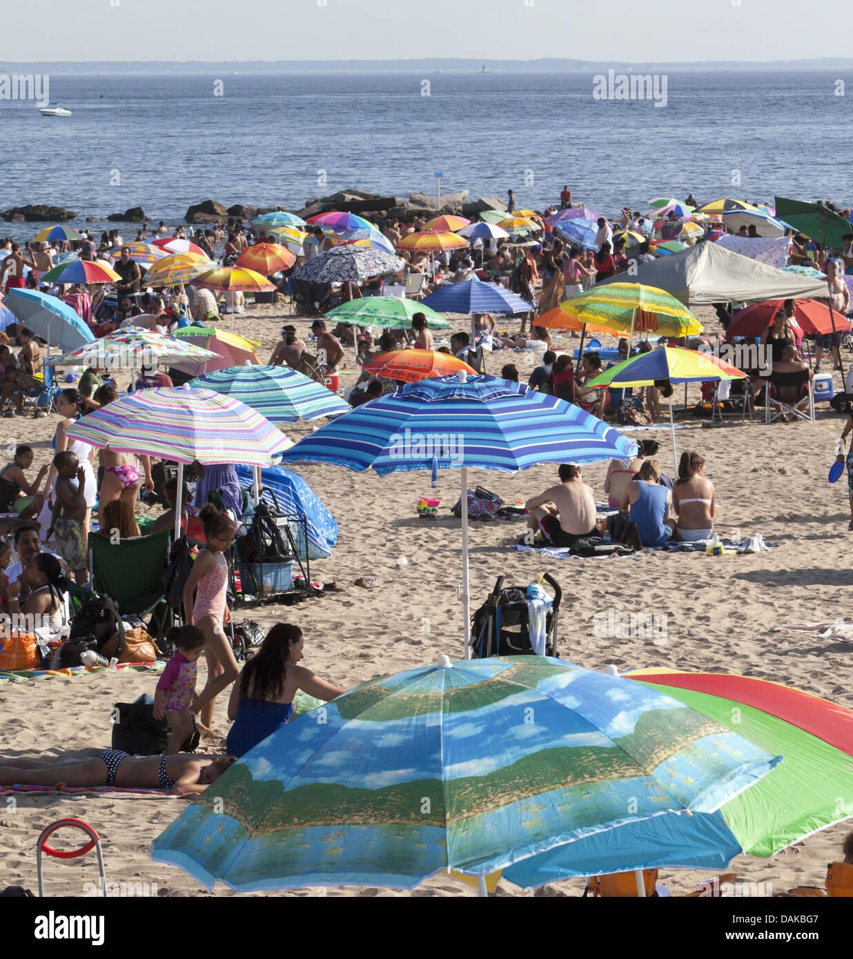 Menschen füllen den Strand mit bunten Sonnenschirmen an einem heißen Sommertag auf Coney Island, Brooklyn, Stockbild