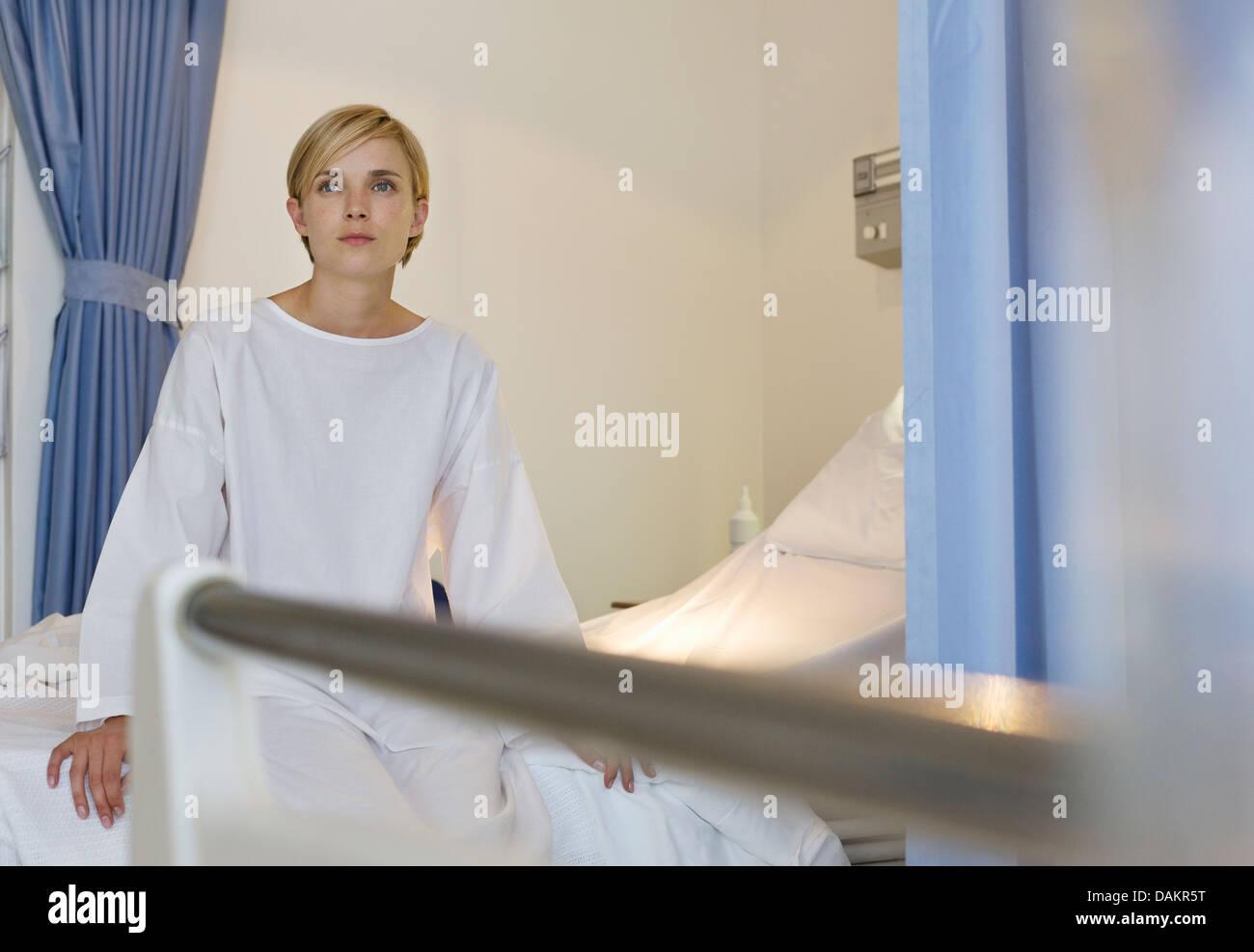Patient sitzt am Krankenhausbett Stockbild