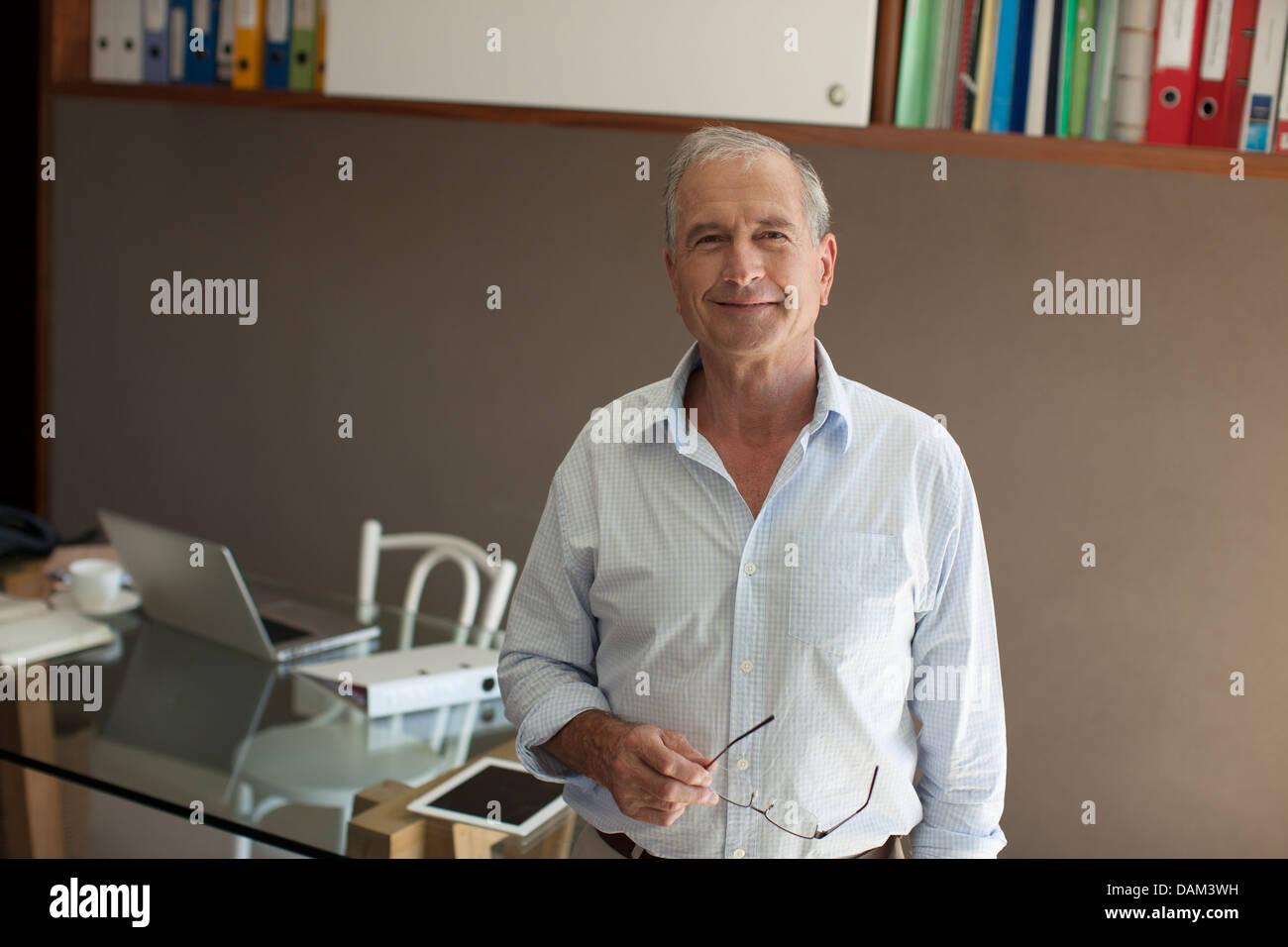 Älterer Mann lächelnd in Büro Stockbild