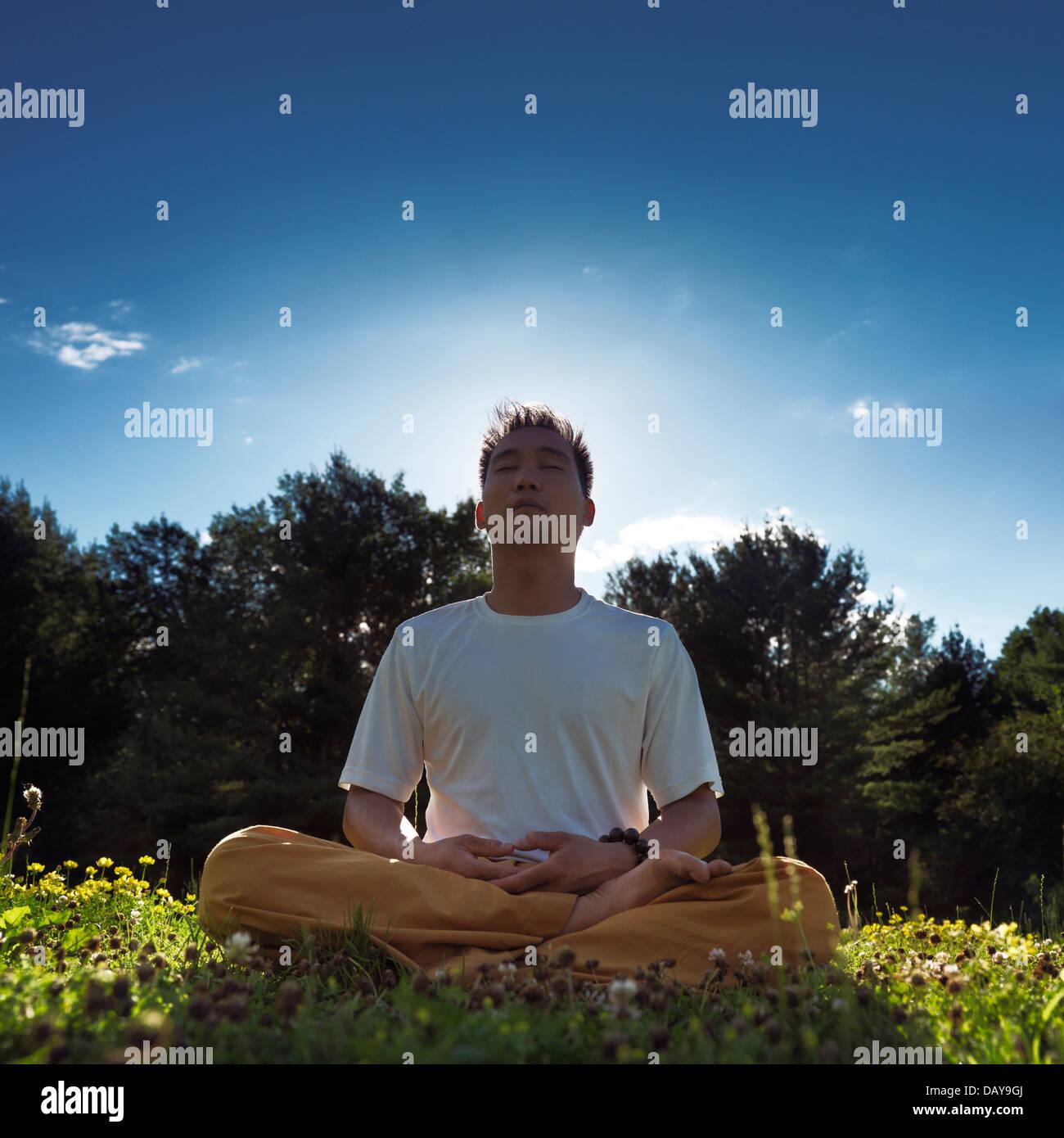 Chinesischer Mann meditieren im Freien bei Sonnenaufgang in der Natur, sitzen mit gekreuzten Beinen auf dem Rasen Stockfoto