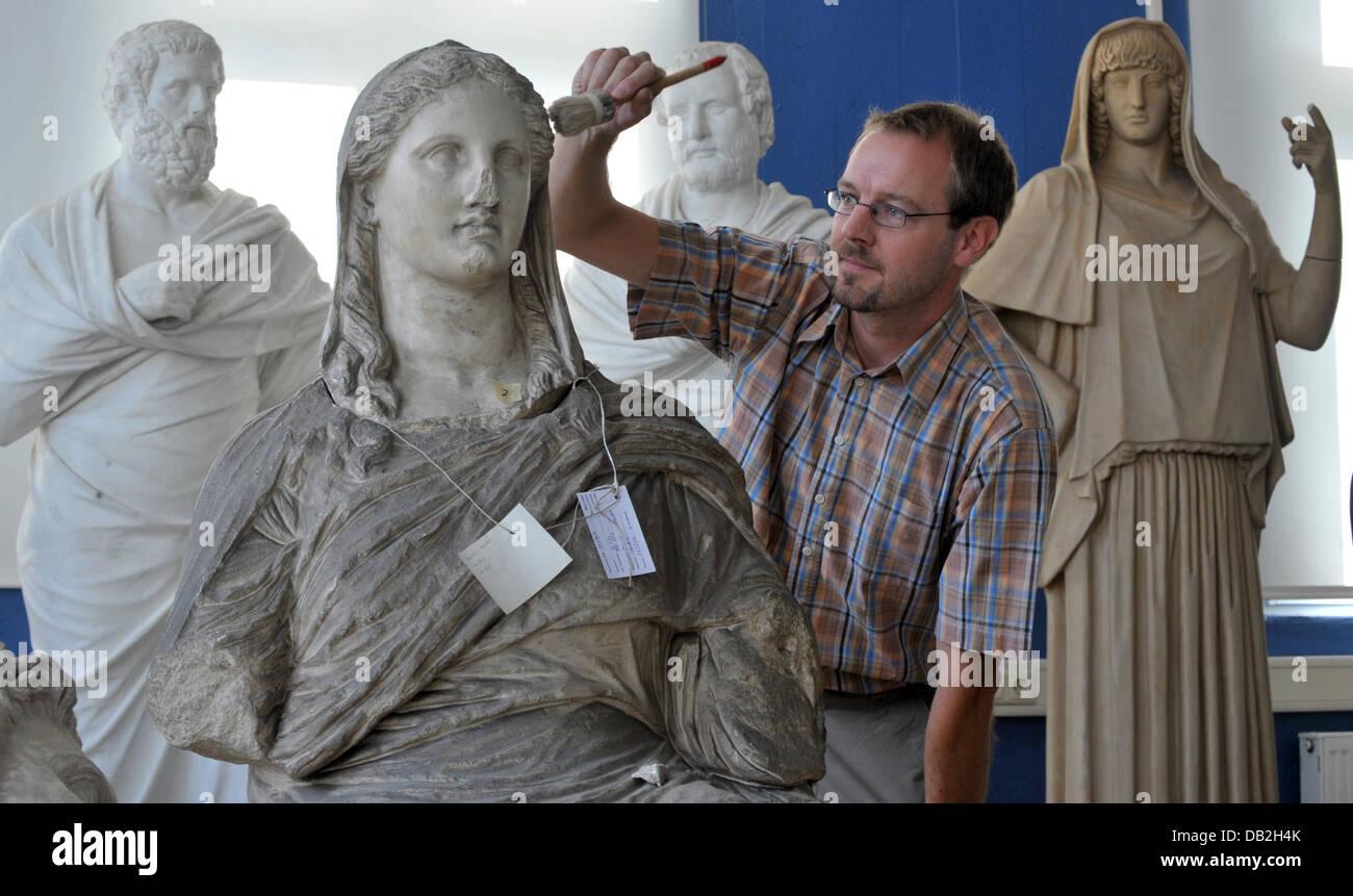 Antiquitäten Jena : Dennis graen reinigt eine skulptur in der sammlung von antiquitäten