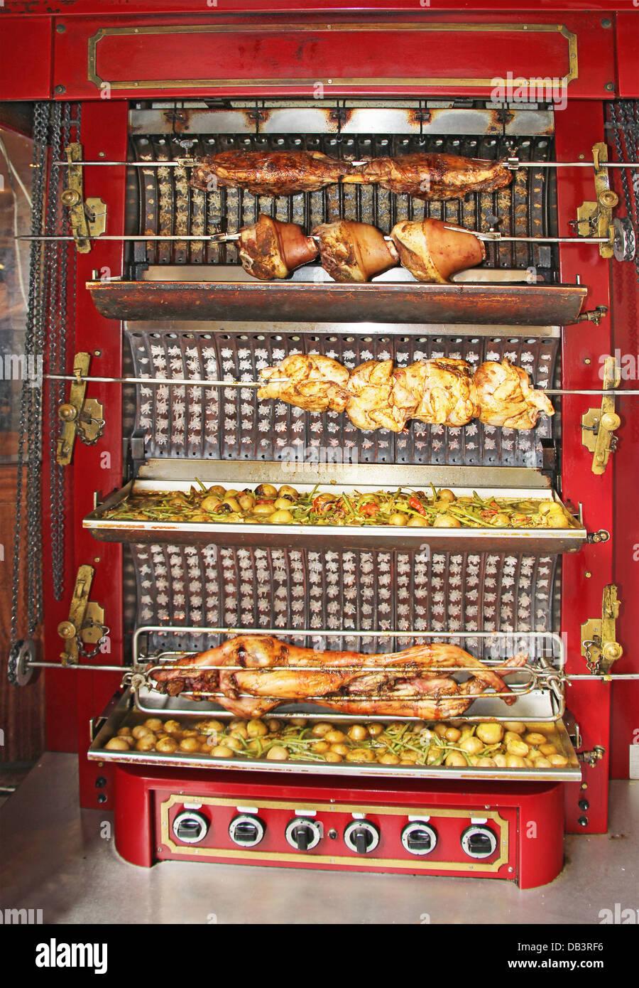 Gebratenes Schwein und Huhn auf der Folterbank Stockbild