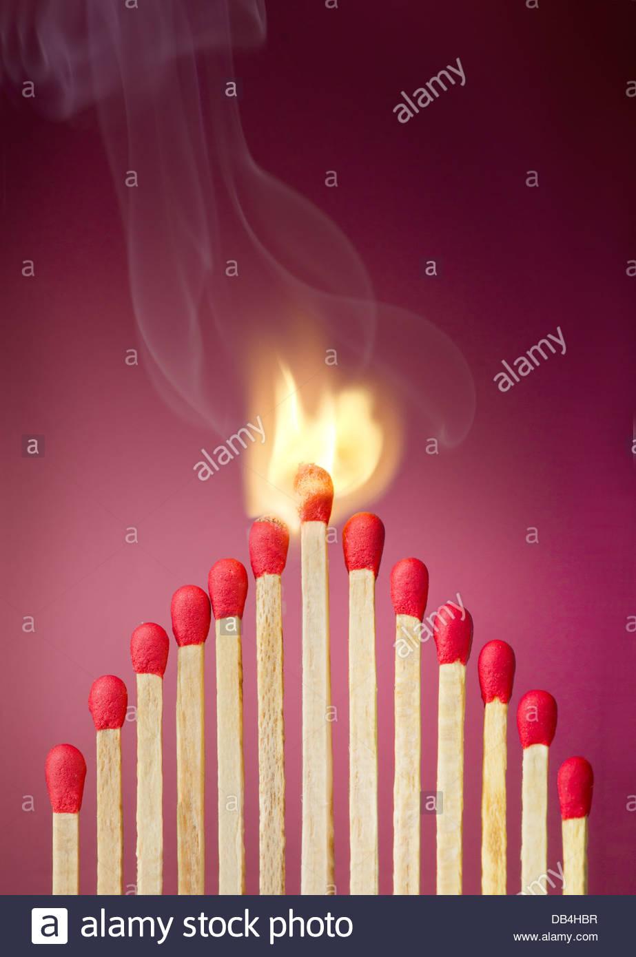 Brennendes Zündholz Brandstiftung in seiner Nachbarn, eine Metapher für Ideen und inspiration Stockbild