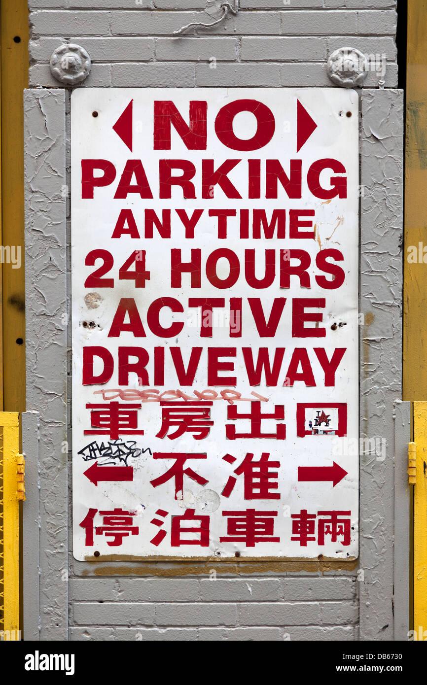 Kein Parkplatz Zeichen in englischer und chinesischer Sprache in New York City Stockbild