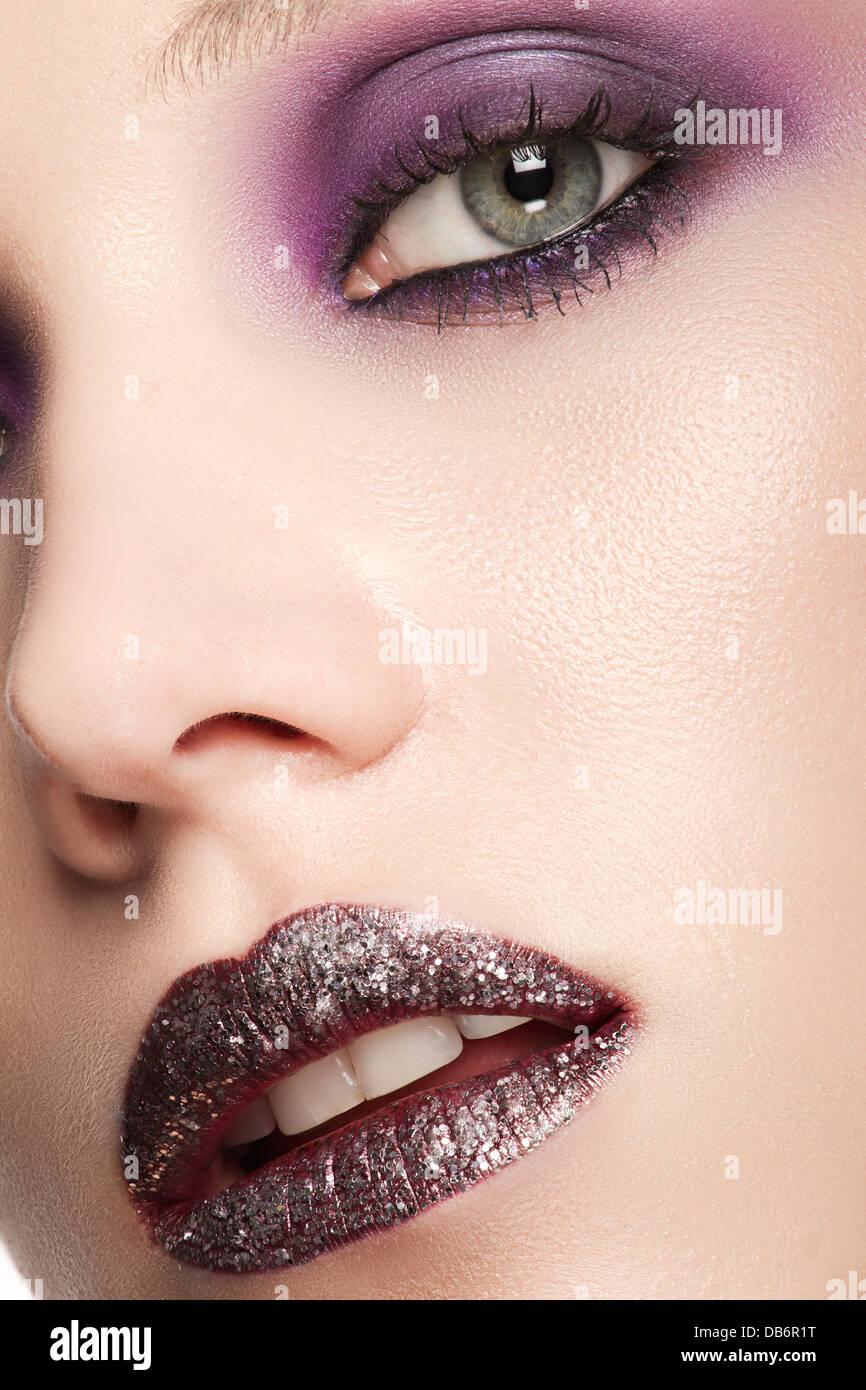 Ein schönes Modell mit lila Lippen und Augen und Glanz auf den Lippen in Nahaufnahme Stockbild