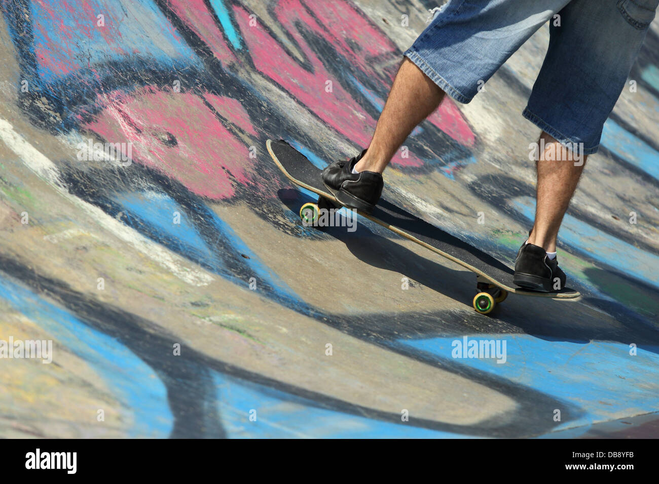 junge rohr beine auf einem skateboard in einem halben mit graffiti stockbild - Skateboard Bank Beine