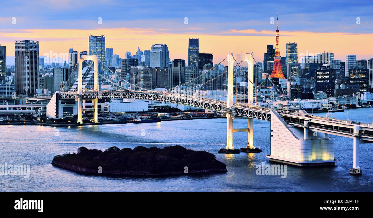 Rainbow Bridge überspannt die Bucht von Tokio mit Tokyo Tower im Hintergrund sichtbar. Stockbild