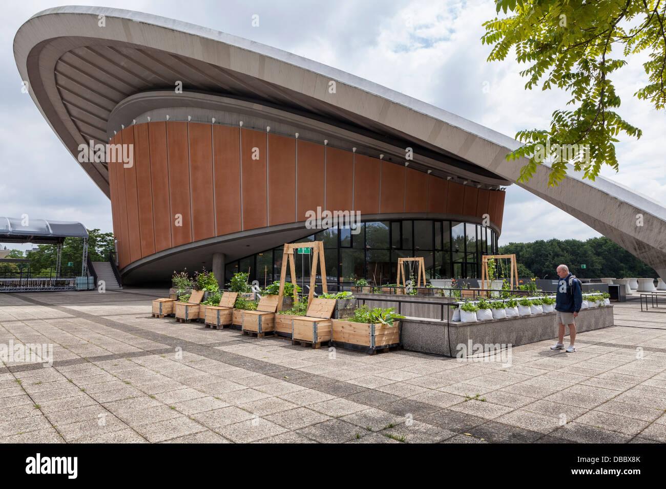 Mann an Kräuter- und Gemüsegarten in aufgearbeiteten Verpackung Kiste Holz HKW Concert Hall und Ausstellung Stockbild