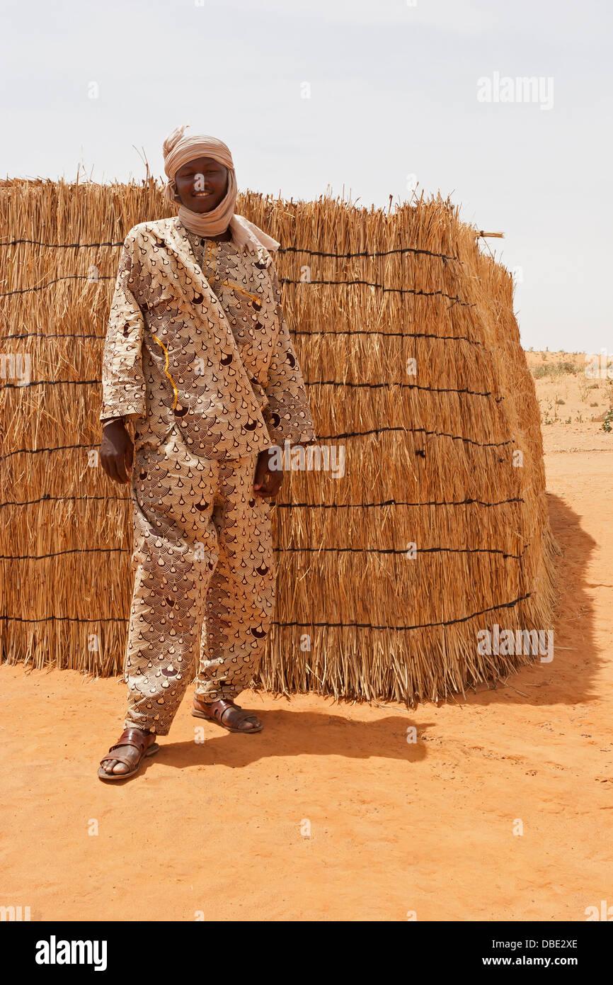 Junge malische Dorf Mann aus Nord-Ost-Mali in traditioneller Kleidung vor Holz gerahmt gewebte Matten Hütte, Stockbild