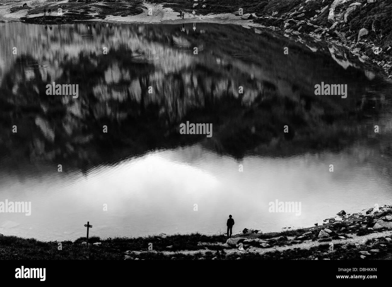 Italien. Ein Mann steht neben einem ruhigen und friedlichen See allein. Stockbild