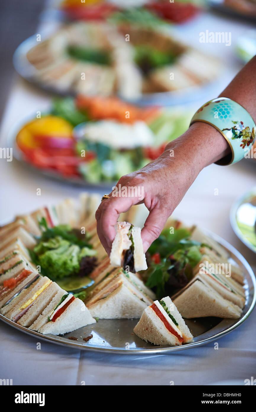 Dame, die Kommissionierung eines Sandwiches Stockbild