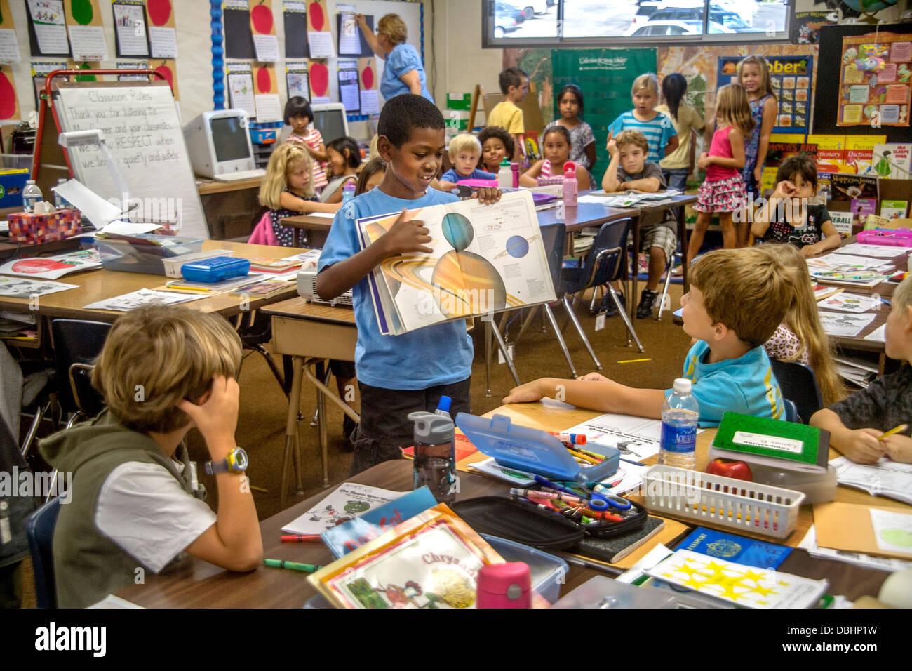 Eine afrikanische amerikanische elementare Schuljunge verwendet eine illustrierte Astronomie-Buch, das Sonnensystem Stockbild
