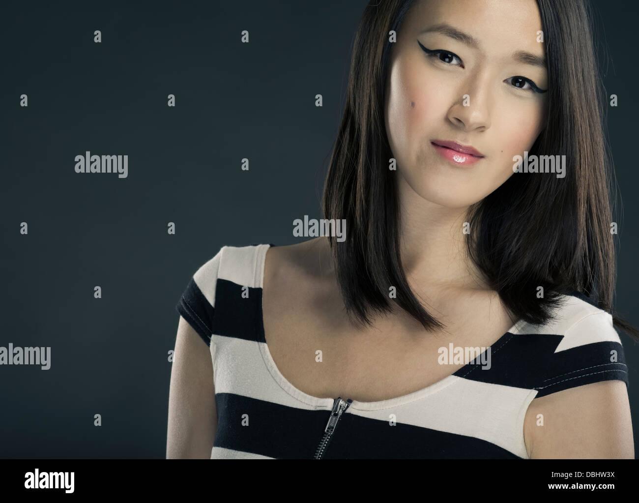 Schöne asiatische Frau mit langen, dunklen Haaren und geflügelten Eye-Liner (Cleopatra-Stil) Stockbild