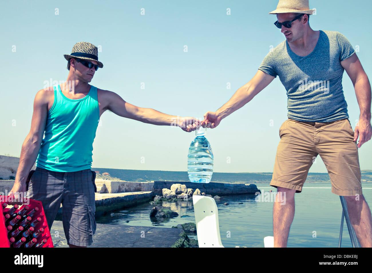 Kroatien, Dalmatien, junge Männer am Meer, den Transport von Bier Stockbild