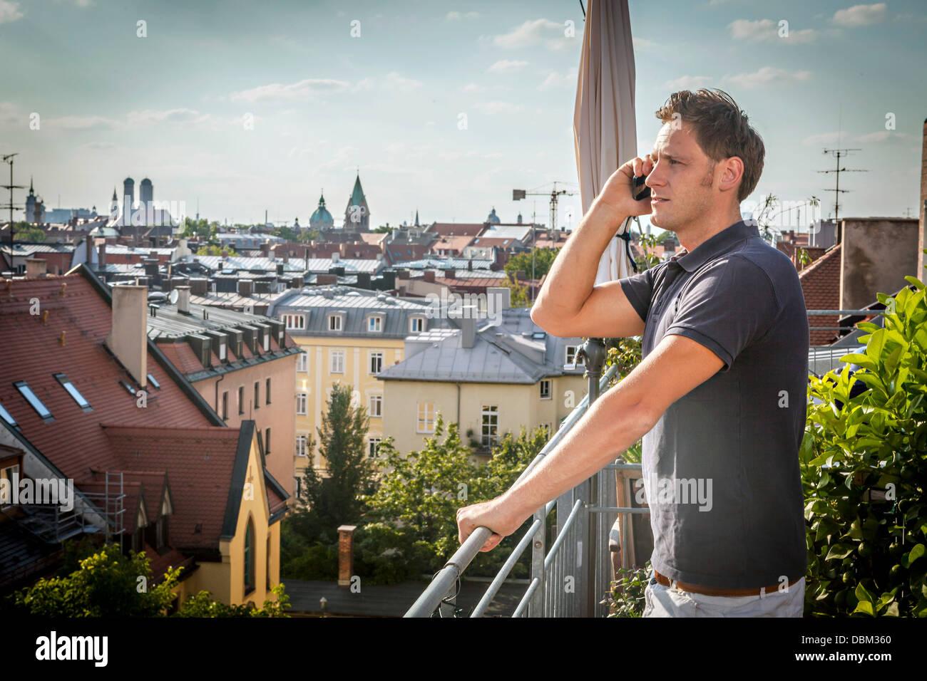 Mann auf Balkon mit Handy, München, Bayern, Deutschland, Europa Stockbild