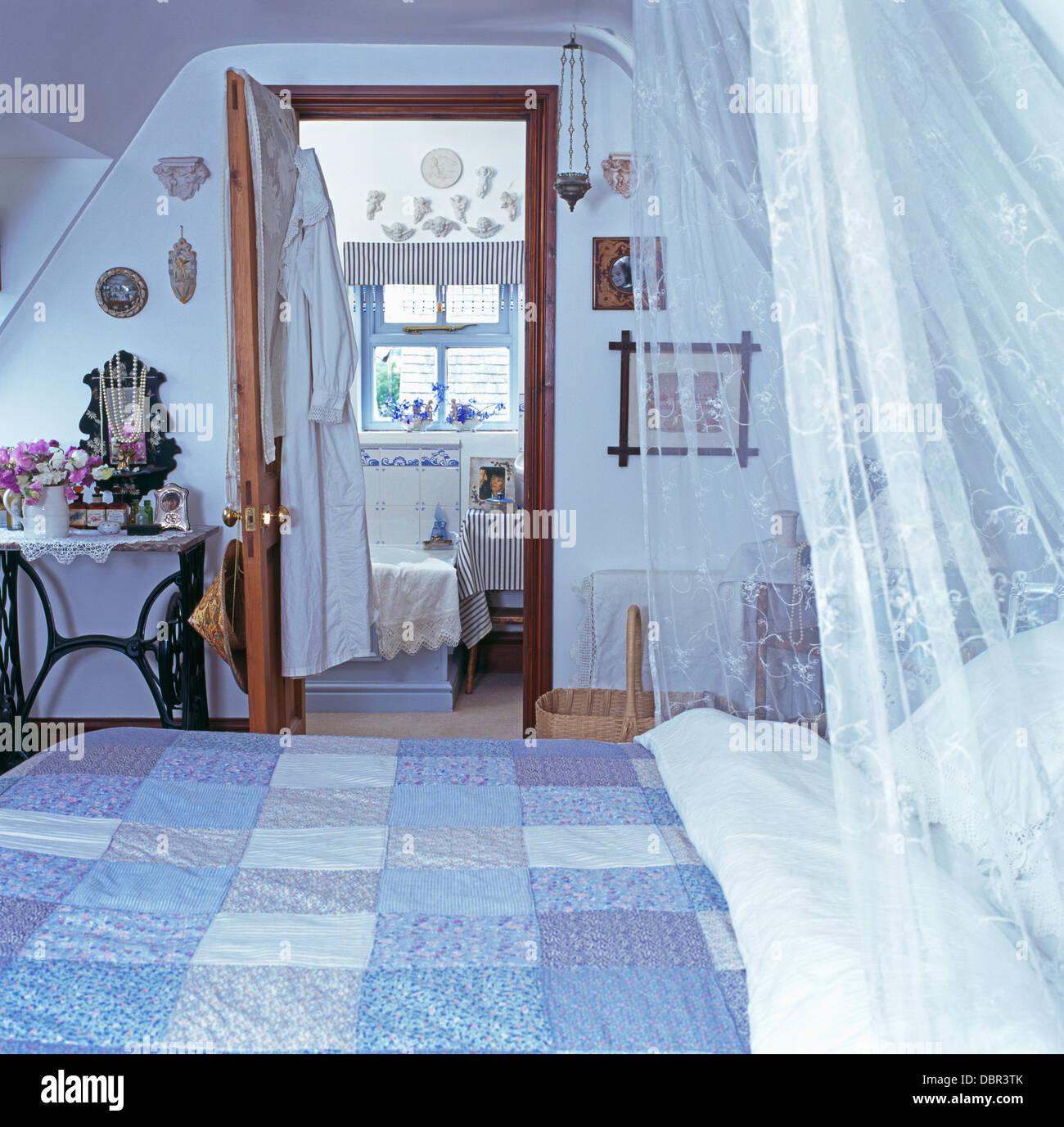 Weißen Voile Vorhänge Und Blauen Patchwork Quilt Auf Bett Im Dachgeschoss  Schlafzimmer Mit Tür Offen Für En Suite Badezimmer