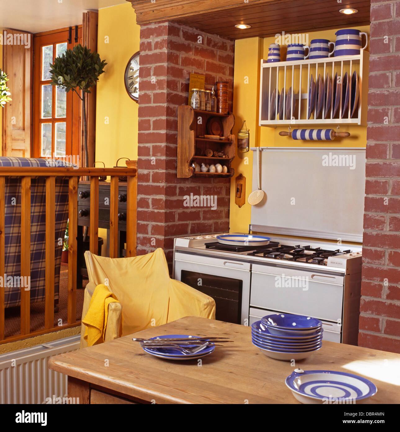 Gelbe Regiestuhl am Tisch mit blauen Gerichte in gelbe Küche mit ...