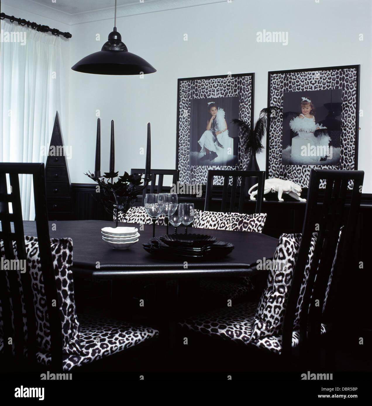 Schwarz + weiß Tier-Print Kissen auf schwarzen Stühlen am schwarzen ...