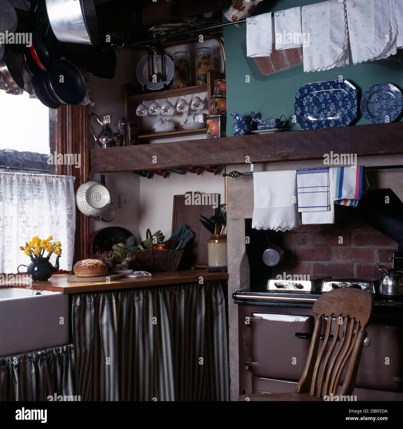Gestreifte Vorhänge an Einheiten in kleinen Cottage-Küche mit Leinen ...