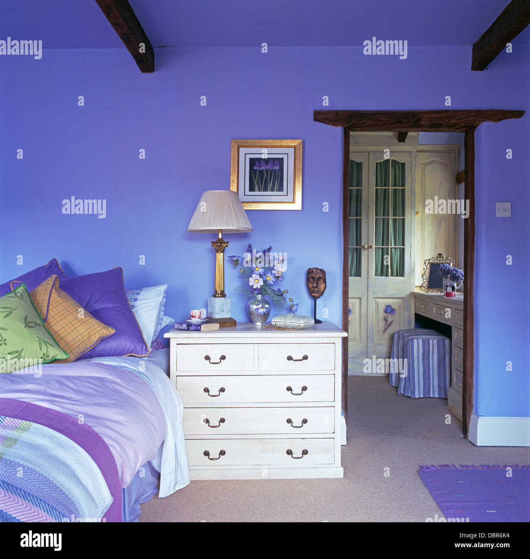 Weiße Kommode Neben Bett Gestapelt Mit Bunten Kissen In Hellen Blauen  Schlafzimmer Mit Tür Zum Bad Offen