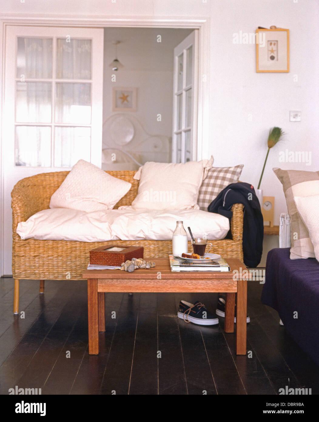 Milchflasche auf einfachen Holztisch vor Wicker Sofa mit ...