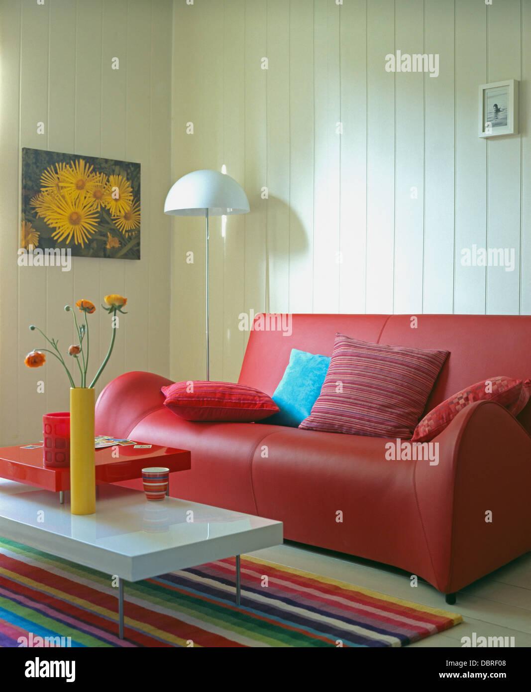 Corian-Spitze Tisch und bunt gestreiften Teppich vor rotem Ledersofa ...