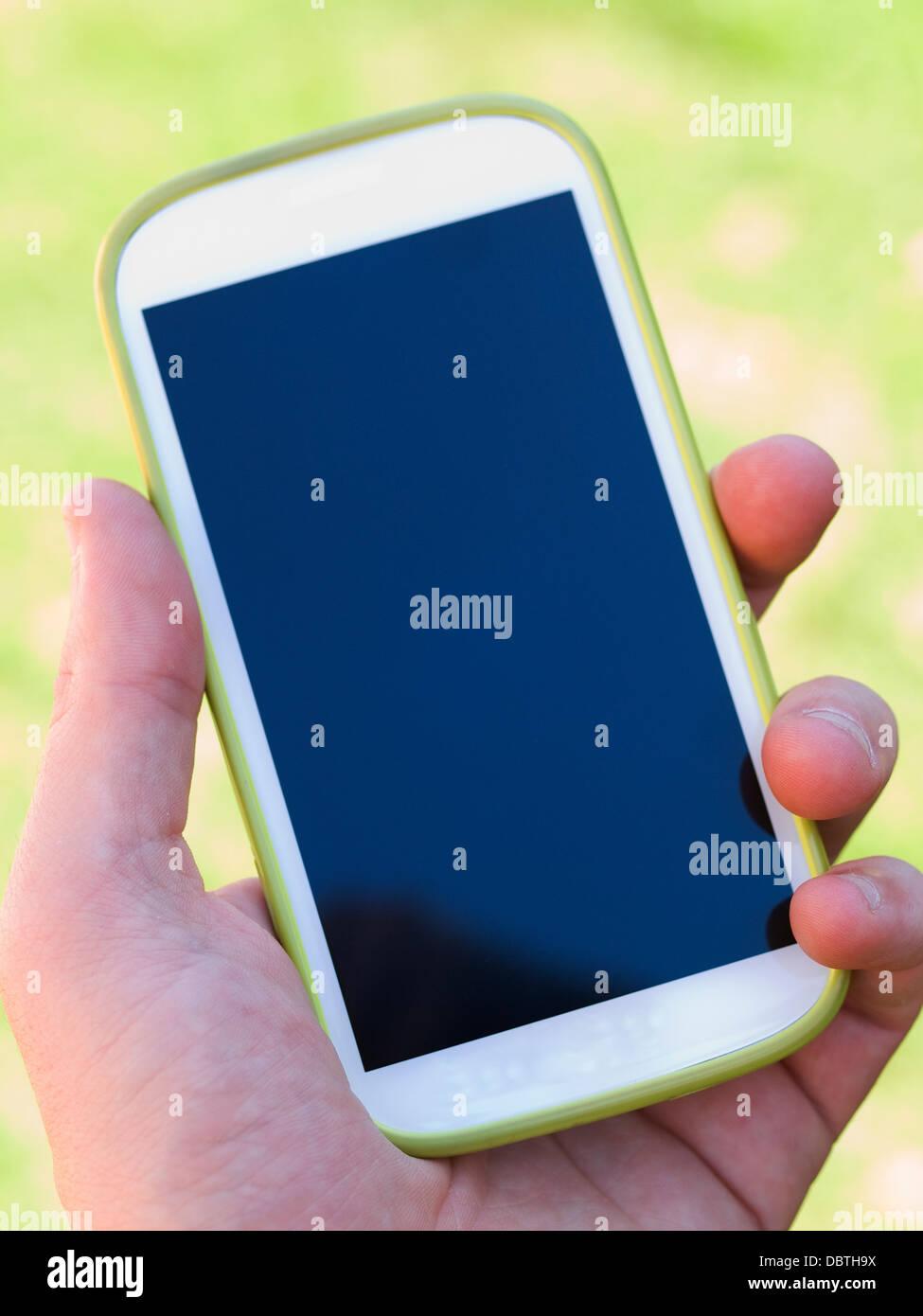 Hand, die eine Smartphone auf natürlichen grünen Hintergrund Stockbild