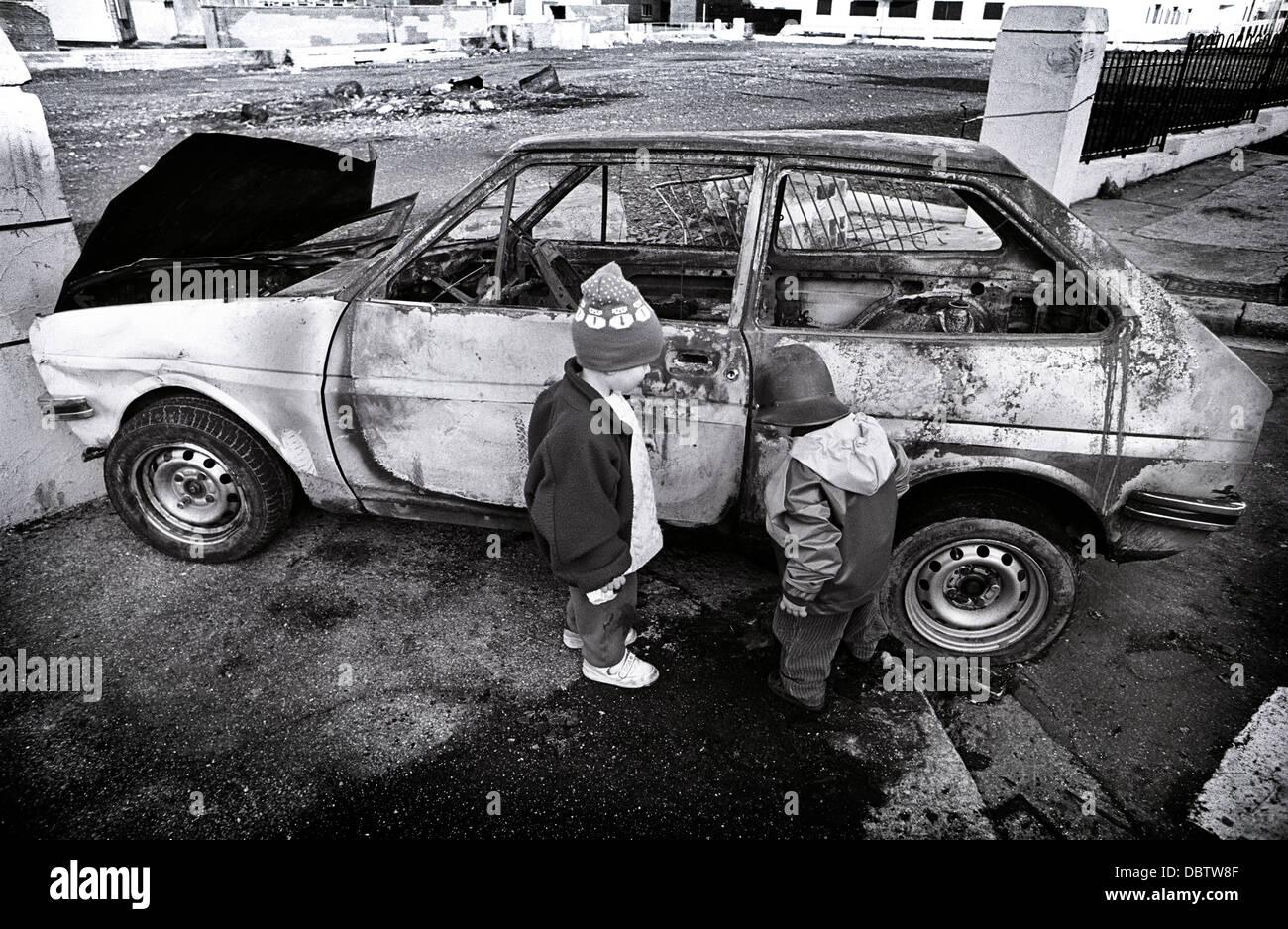 Kinder spielen in der Nähe von einem ausgebrannten Auto in Devonport, England. Anfang der neunziger Jahre Bild. Stockbild