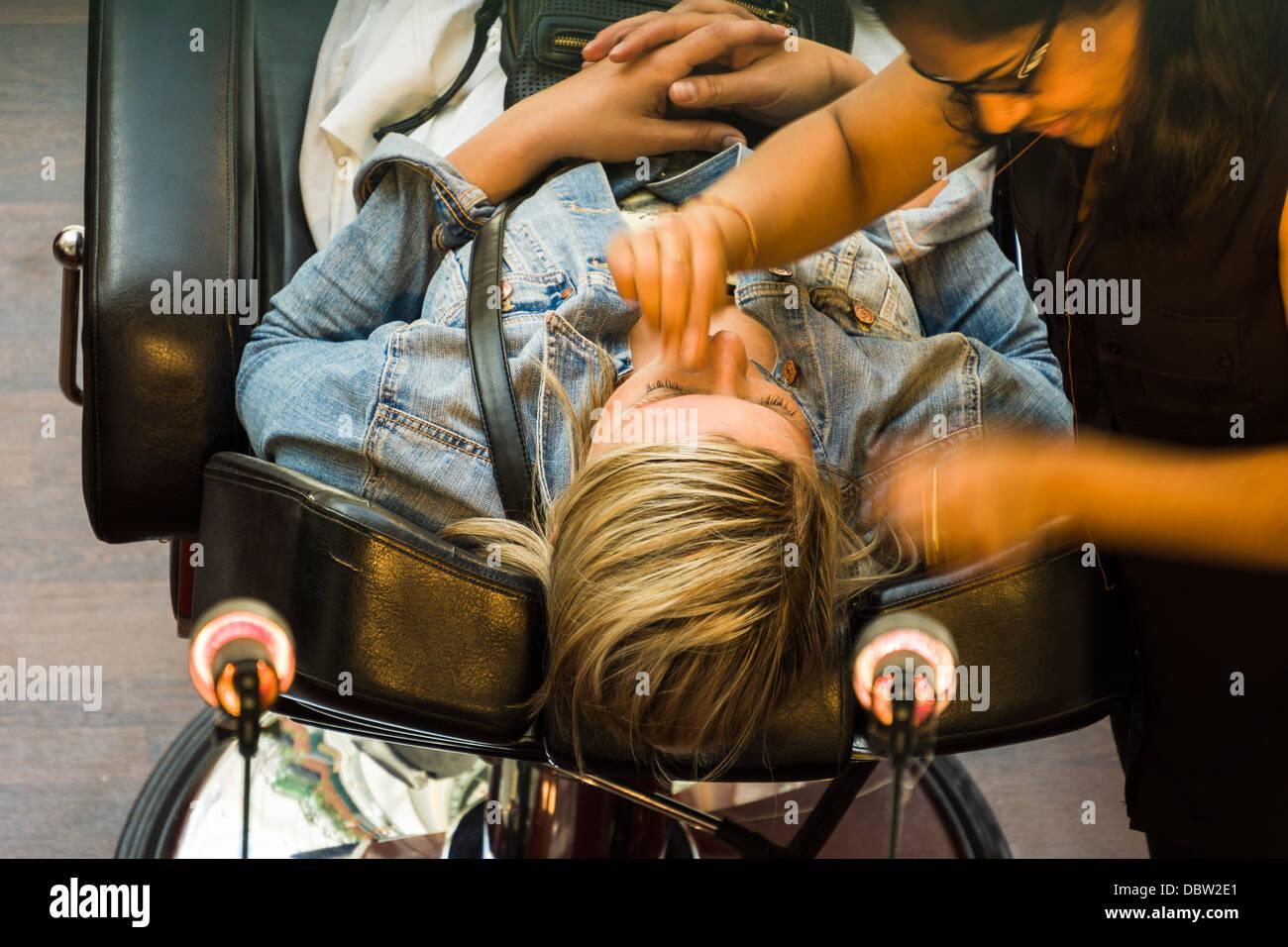 Eine Dame erhält eine Gesichtspflege-Behandlung von einem in-Store Kosmetikerin. Stockbild
