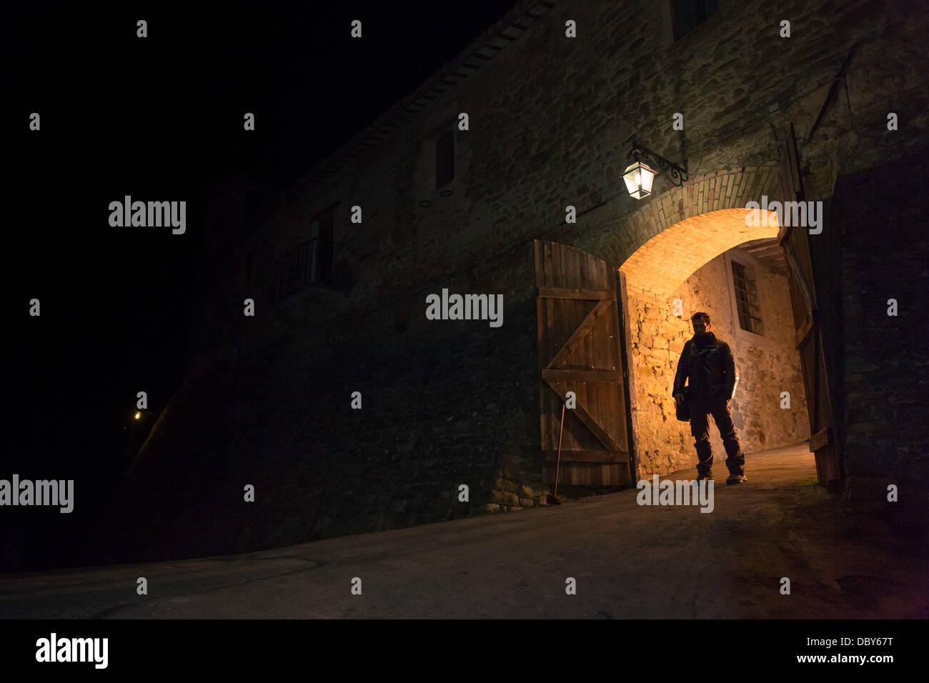 Mann stand vor dem Tor der mittelalterlichen Stadt Stockbild