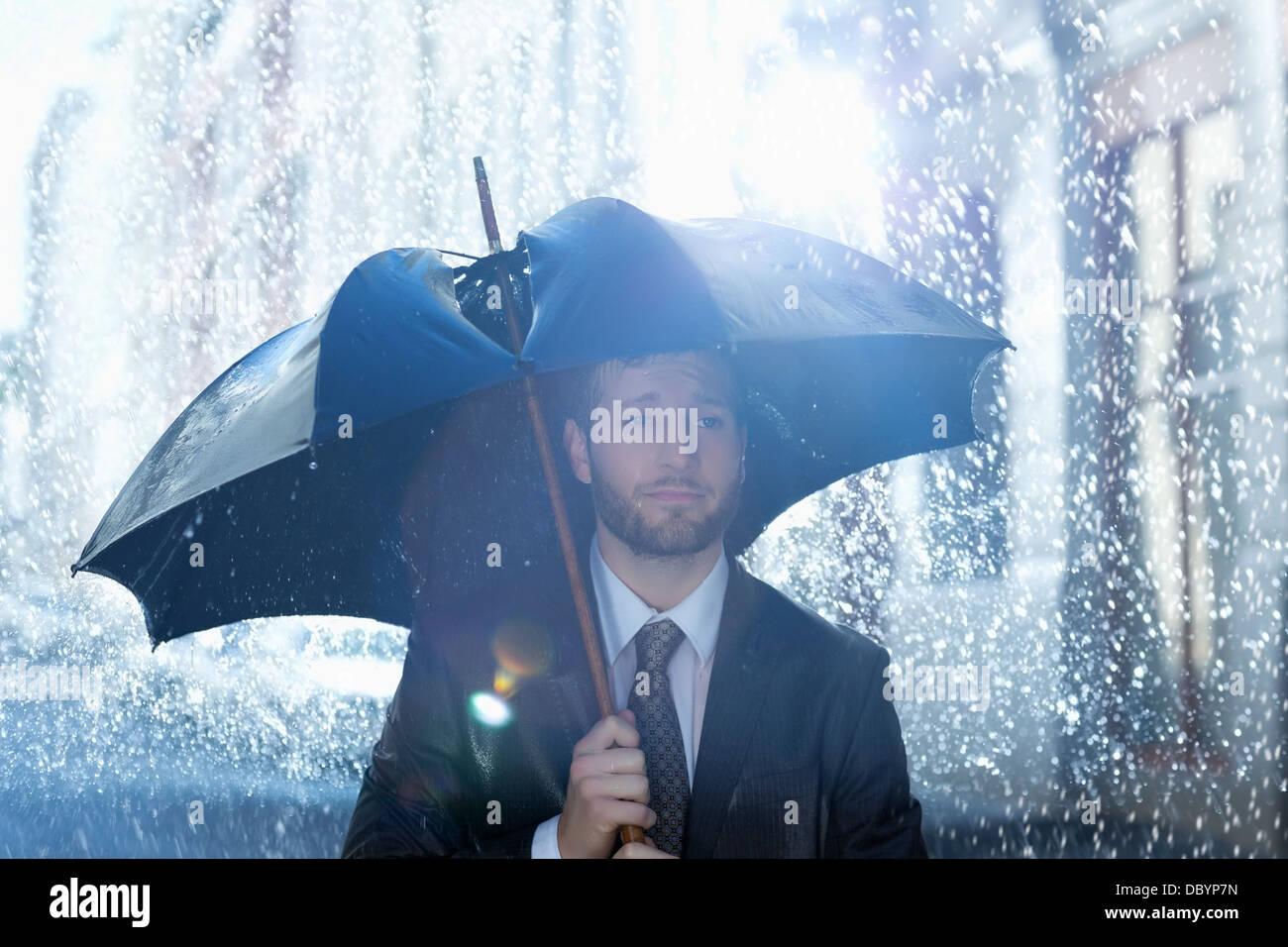 Frustriert Geschäftsmann mit gebrochenen Schirm im Regen Stockbild