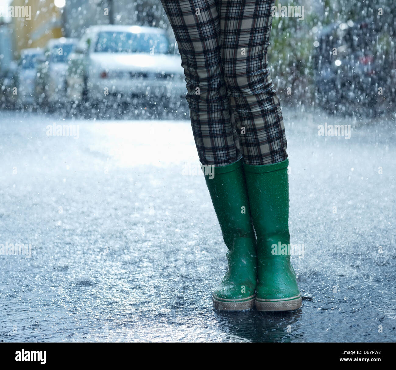 Regen fällt um Frau in Gummistiefel Stockbild
