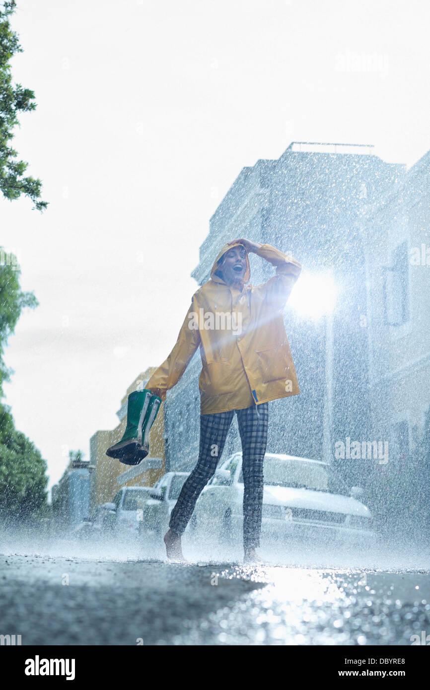 Frau im Regenmantel tragen Gummistiefel und barfuß im Regen Stockbild