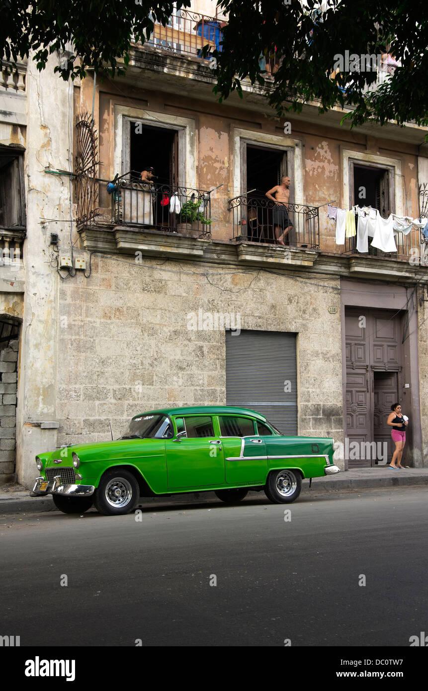 Centro Habana-Altbau-Wohnung, Mann im oberen Fenster, Frau an der Tür, zwei getönten grünes Auto Stockbild