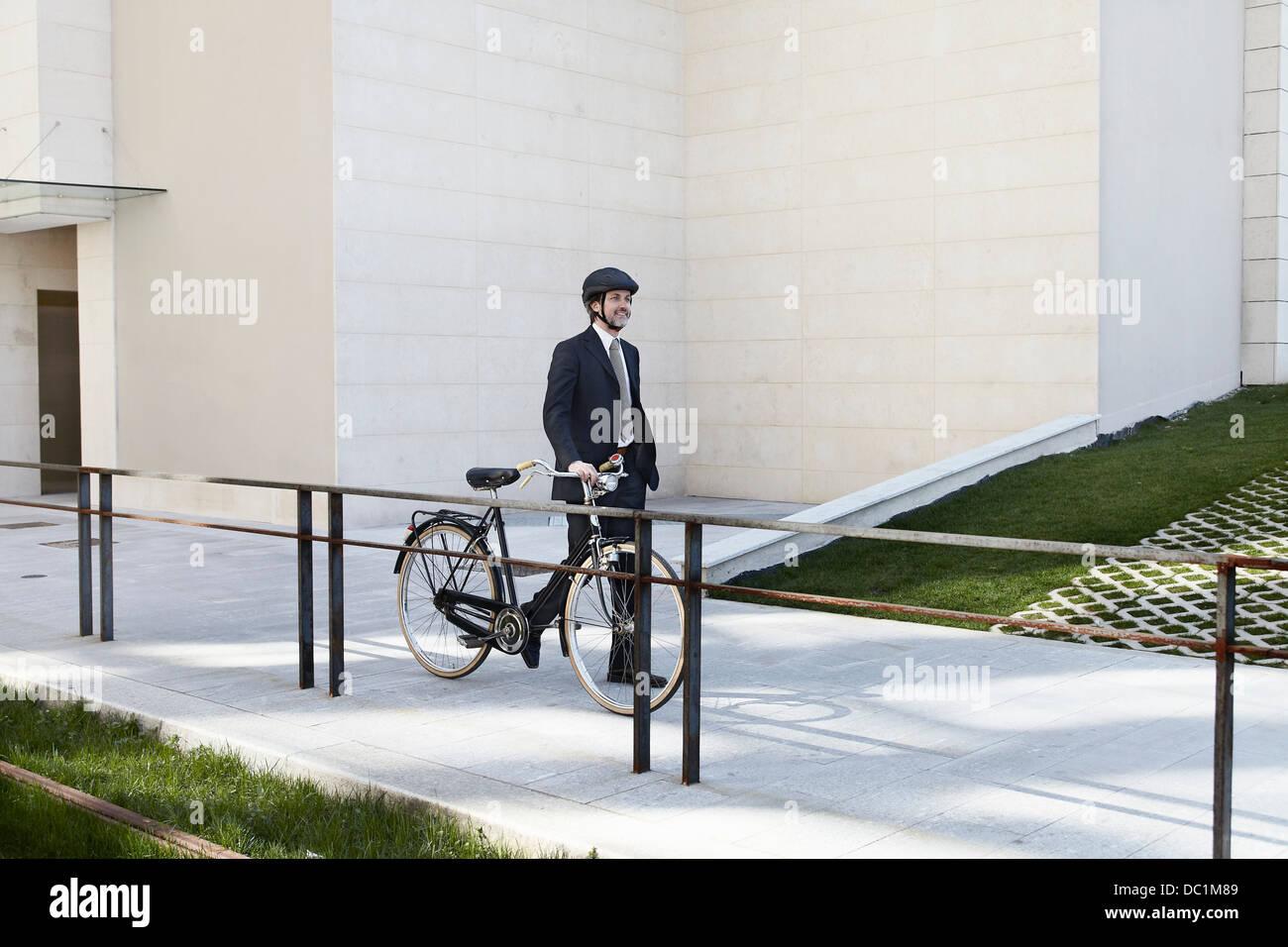 Mitte adult Geschäftsmann zu Fuß mit dem Fahrrad Stockbild