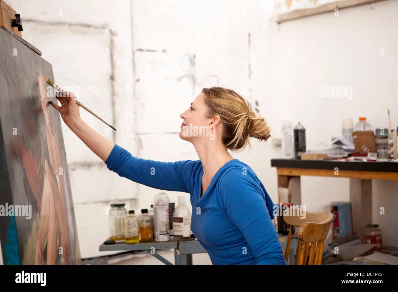 Mitte Erwachsene Frau malen auf Leinwand im Atelier des Künstlers Stockbild